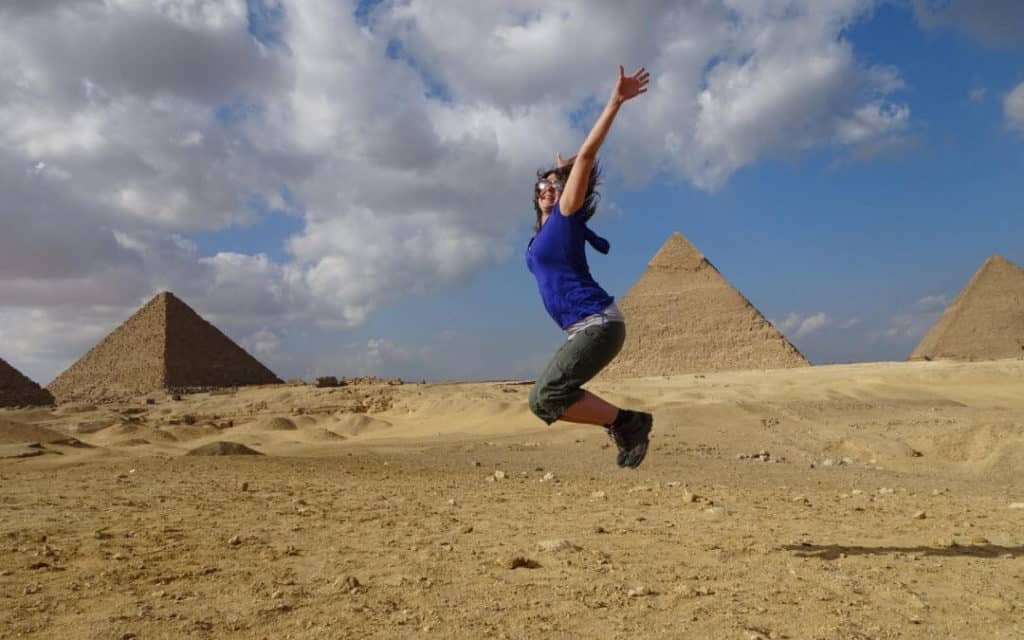 Sarah jumping in front of the pyramids of Giza