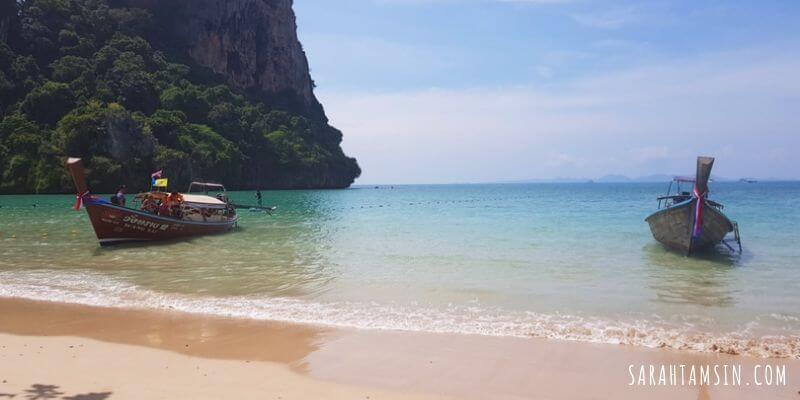 2 longtail boats on crystal clear blue water with blue skies in Railay